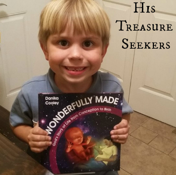 Deanna's son of His Treasure Seekers with their copy of Wonderfully Made: God's Story of Life from Conception to Birth for kids from ages 5-11.