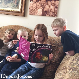 Gena's kids from I Choose Joy with their copy of Wonderfully Made: God's Story of Life from Conception to Birth for kids from ages 5-11.